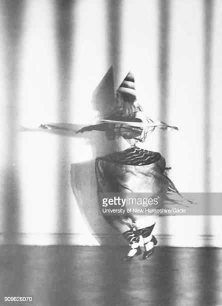 Black and white photograph of dancer Lieselotte Felger wearing a conical hat a diaphanous top and trousers and dance shoes spinning against a blank...