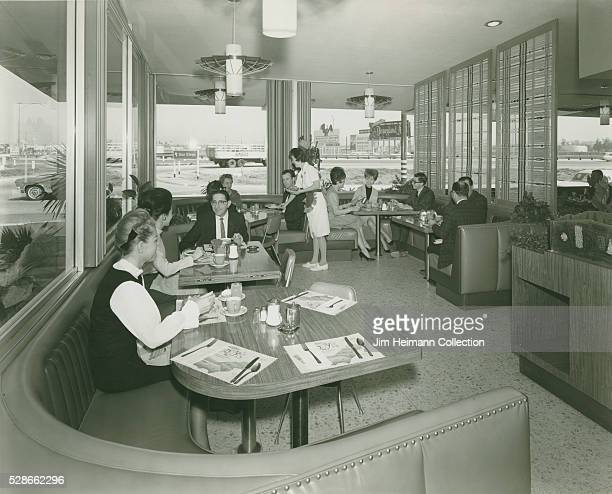 Black and white photograph of diners sitting at tables in restaurant with large picture windows