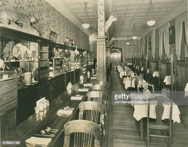 Black and white photograph of empty restaurant with taxidermy animals