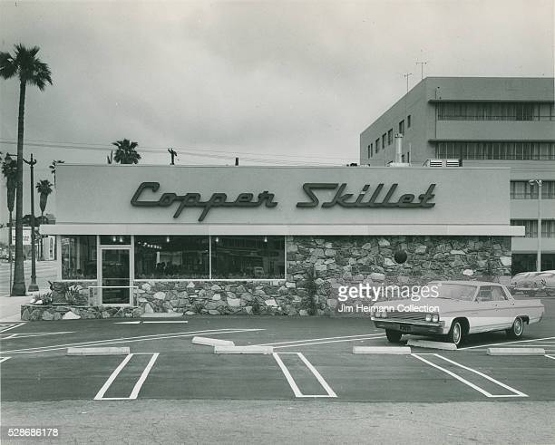 Black and white photograph of exterior of Copper Skillet restaurant with car in parking lot and palm tree