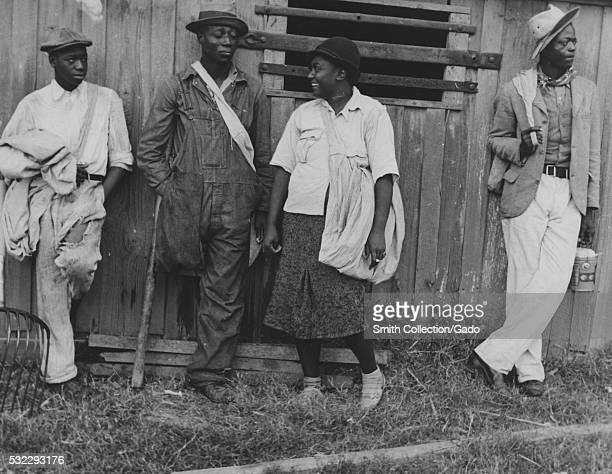 Black and white photograph of four cotton pickers three AfricanAmerican men one AfricanAmerican woman standing outside against a wall Arkansas 1877...