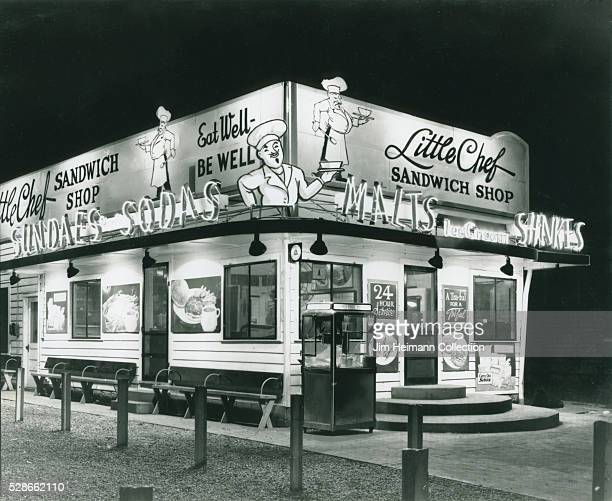 Black and white photograph of Little Chef Sandwich Shop exterior at night with neon signs illuminated