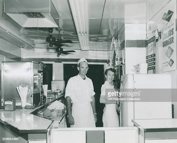 Black and white photograph of man and woman working behind counter at Orange Julius