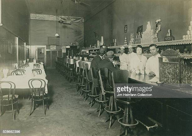 Black and white photograph of men sitting at restaurant counter staff standing behind counter