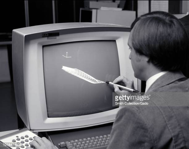 Black and white photograph of Paul Kutler, using a light pen and keyboard to work on a vector graphics project using an IBM 2250 Graphics Display...