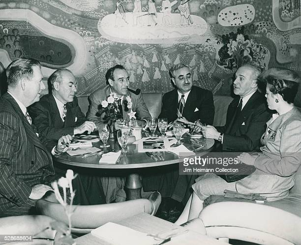 Black and white photograph of people sitting at round booth in restaurant