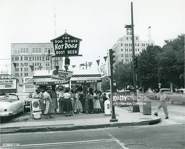 Black and white photograph of people standing at Dog House hot dog stand on busy urban street with tall buildings in background