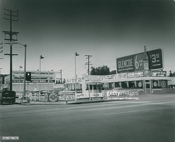 Black and white photograph of restaurant with parking lot and large billboard
