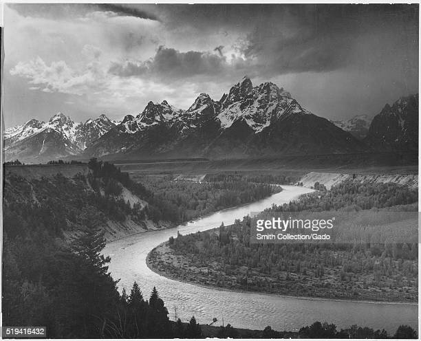 A black and white photograph of several of the peaks of the Teton Range covered in snow the Snake River winds through the landscape and is surrounded...