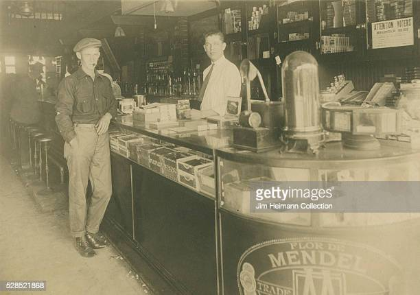 Black and white photograph of staff and patron standing by glass counter