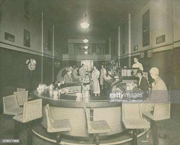 Black and white photograph of staff and patrons at circular counter in BG Sandwich Shop