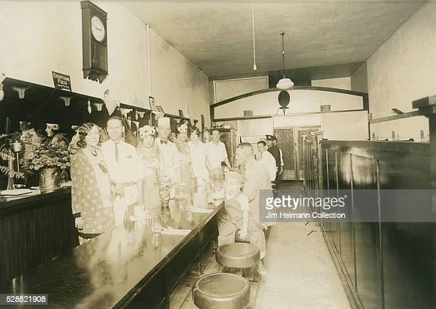Black and white photograph of staff and patrons posed by bar in restaurant