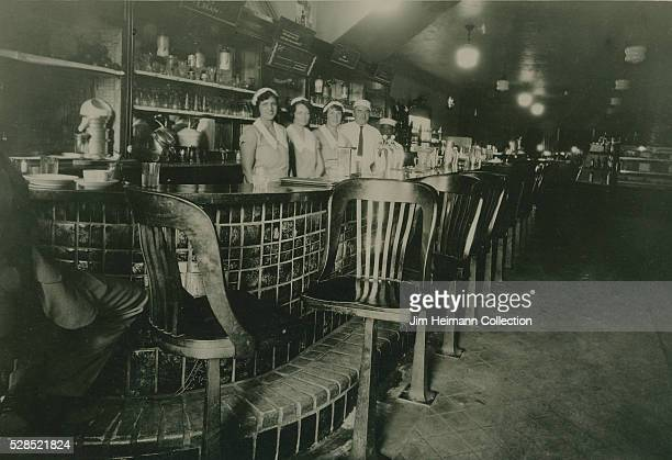 Black and white photograph of staff in uniform posed standing behind bar No patrons