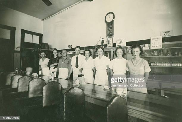 Black and white photograph of staff standing behind wooden counter with click in background