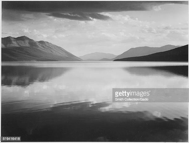 A black and white photograph of the flat surface of McDonald Lake in Glacier National Park the background of the images consists of several tall...