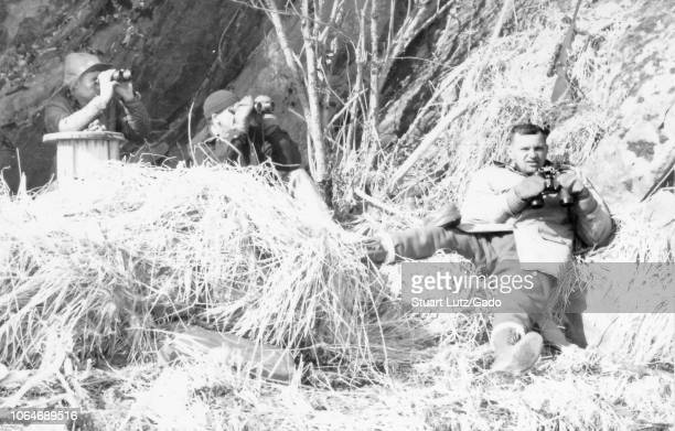 Black and white photograph of three middleaged men in an outdoor setting with dry grasses and branches on the ground and a rocky hill or cliff in the...