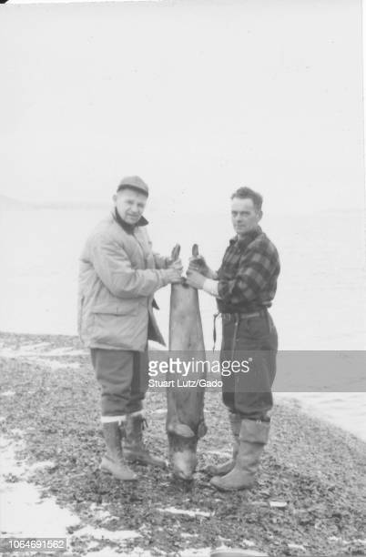 Black and white photograph of two middleaged men one wearing a jacket cap and laceup boots the other wearing a plaid shirt and fishing boots standing...