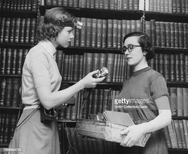 Black and white photograph of two slim darkhaired young women likely librarians standing in profile facing each other the woman at left who wears a...