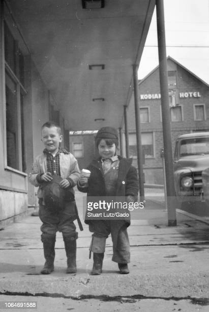 Black and white photograph of two small smiling boys standing together in fulllength view on a sidewalk in downtown Kodiak Alaska both wearing warm...