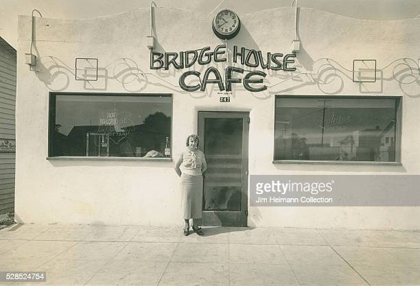 Black and white photograph of woman standing by doorway Bridge House Cafe with clock face and adobe facade