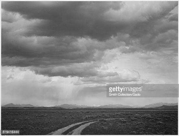Black and white photograph roadway low horizon mountains clouded sky captioned 'Near Teton National Park' by Ansel Adams from Photographs of National...