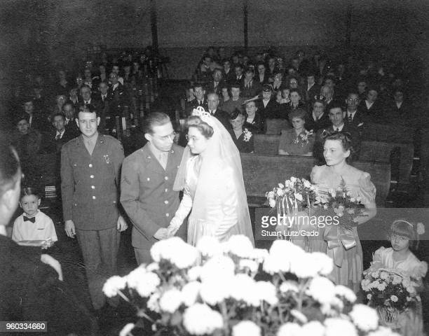 Black and white photograph shot from behind the right shoulder of a marriage officiant showing a groom in a military uniform standing next to a bride...