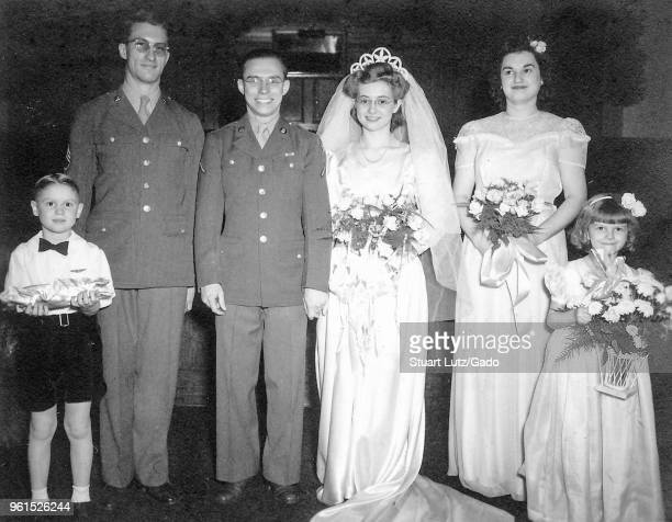 Black and white photograph showing a groom in a military uniform and glasses standing next to a bride wearing a white dress veil tiara and glasses...