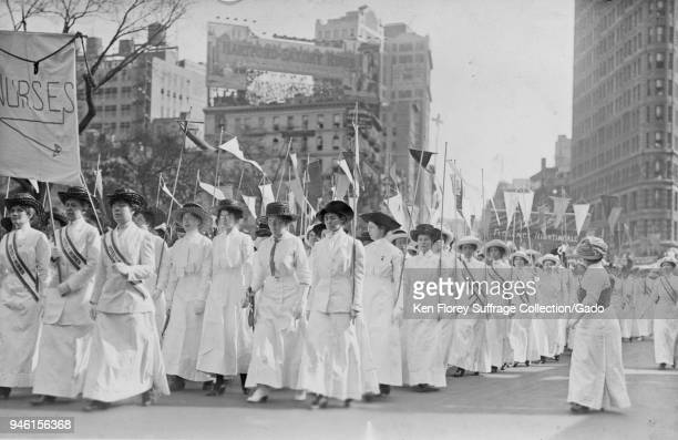 Black and white photograph showing a group of nurses wearing white Edwardian clothing and sashes reading 'Votes for Women ' and holding pennants...