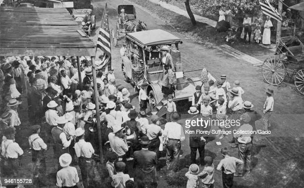 Black and white photograph showing a group of suffragists riding a float fashioned from a Liberty Bell cast on a truck bonnet surrounded by a crowd...