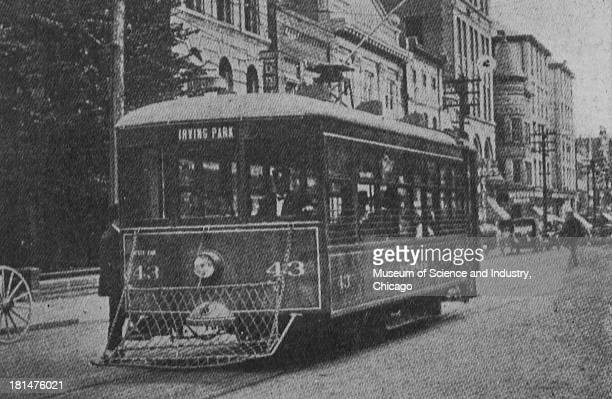 Black and white photograph showing a Safety Car Number 43 driving along Greensboro's Business District with its destination being Irving Park...