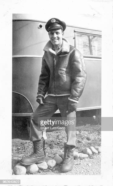 Black and white photograph showing a smiling man in full length standing outdoors wearing an sheepskin lined leather aviator or bomber jacket...
