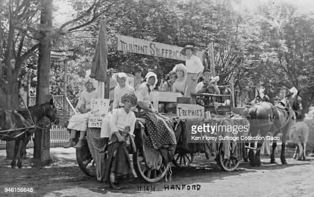 Black and white photograph showing men and boys some dressed in women's Edwardian clothing seated and standing on a horsedrawn antisuffrage float...