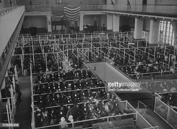 Black and white photograph showing the pens at the Ellis Island Registry Room , all filled with immigrants, by Edwin Levick, Ellis Island, New York,...