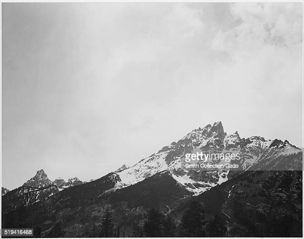 Black and white photograph snow covered peak captioned 'In Grand Teton National Park' by Ansel Adams from Photographs of National Parks and Monuments...