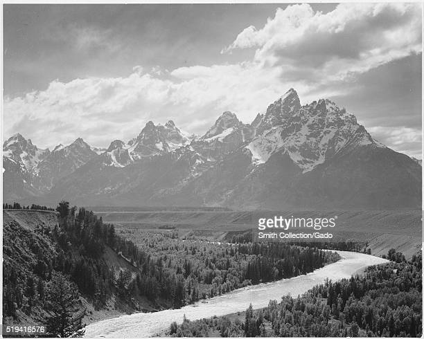 Black and white photograph view from river valley towards snow covered mountains river in foreground from left to right captioned 'Grand Teton...