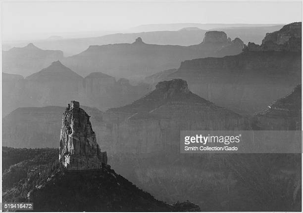 Black and white photograph view with rock formation in foreground captioned 'Grand Canyon National Park' by Ansel Adams from Photographs of National...