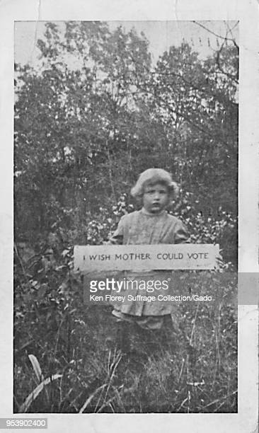 Black and white photographic postcard depicting a small child wearing Edwardian clothing standing outdoors in a field and holding up a sign reading...