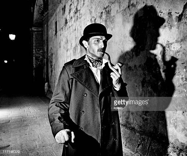 black and white picture of a detective smoking his pipe - sherlock holmes stock pictures, royalty-free photos & images