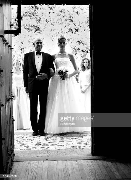 black and white portrait of a bride entering the church with her father