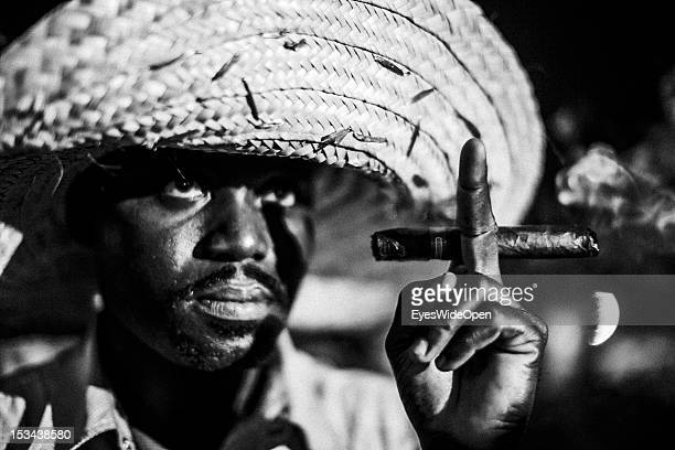 Black and white portrait of a local bahamian man, a smoker, who is wearing a big straw hat and is smoking a cigar at the annual Rake 'n' Scrape...