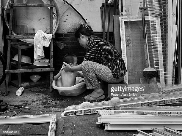 Black and white portrait of a mother washing a small boy in a plastic bowl outside a small shop making window frames taken on the streets of Shanghai
