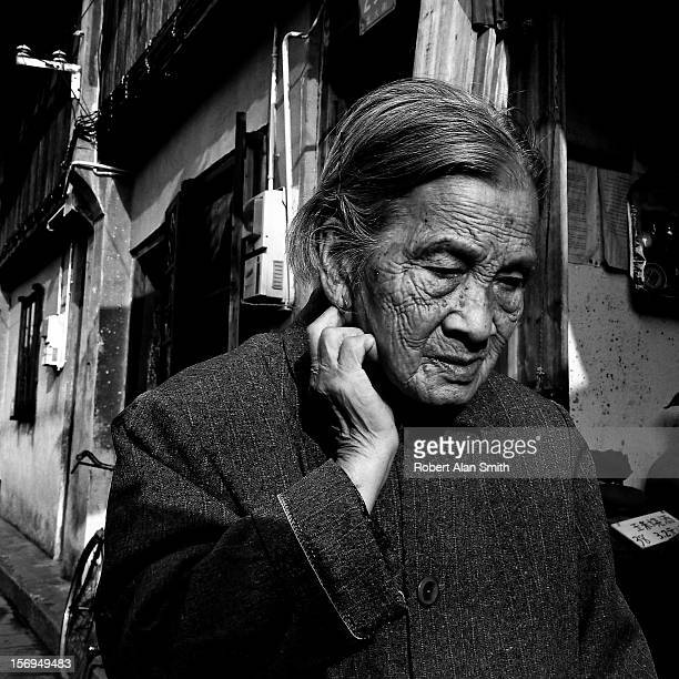 Black and White portrait of an elderly women in the old lanes of Shanghai The portrait shows a face that has endured a lot of life