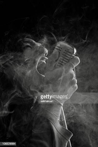 black and white portrait of rock star singing on microphone - metal music stock photos and pictures