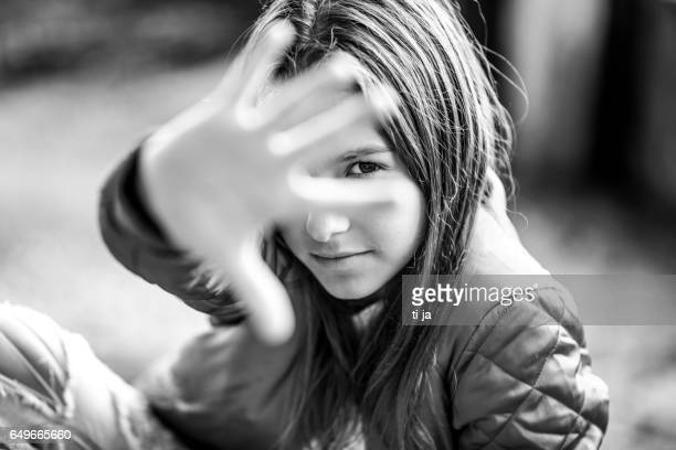 Black and white portrait of teenage girl hiding behind her hand