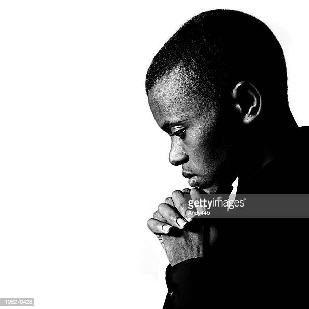 Black and white portrait of young man praying