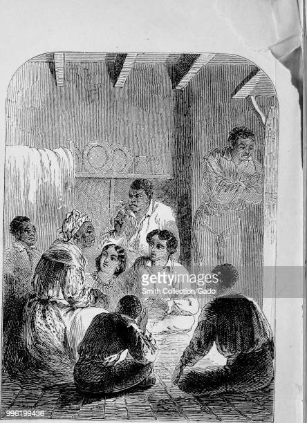 Black and white print depicting a group of AfricanAmerican slaves inside a cabin standing and sitting crosslegged on the floor around an older woman...