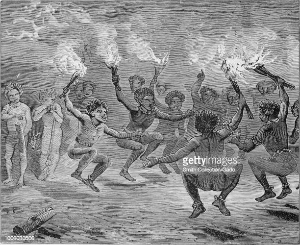 Black and white print depicting a group of New Guinean men holding lit torches and dancing in a circle while other figures look on from the...