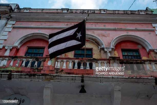 A black and white Puerto Rican National flag hangs from a balcony in Old San Juan Puerto Rico on April 7 2020 On March 15 Puerto Rico Governor Wanda...