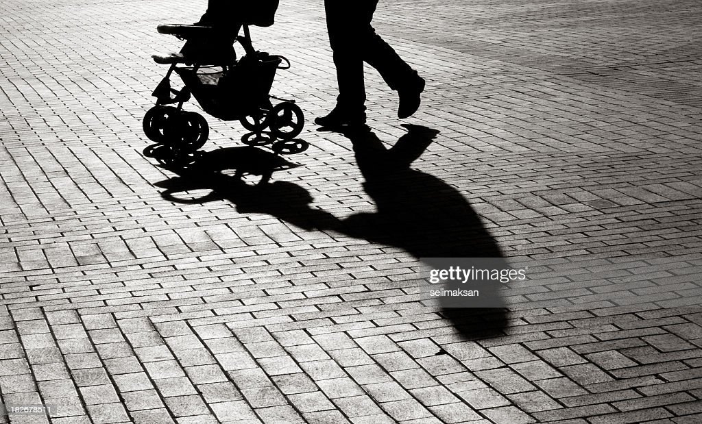 Schwarze und weiße Schatten Kinderwagen auf Gehweg Steinen : Stock-Foto