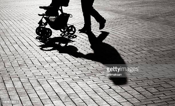 black and white shadow of baby carriage on sidewalk stones - onherkenbaar persoon stockfoto's en -beelden